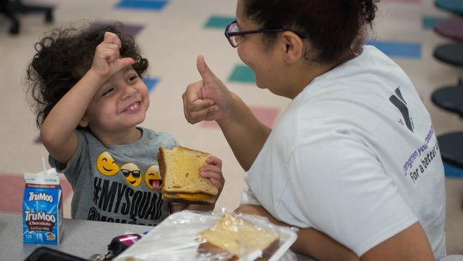 Dilovan Silevani, 3, gives a thumbs-up review of his meal to his mother Julia Silevani, both of Nashville, while participating in a summer meals program at Whitsitt Elementary School on Tuesday, June 5, 2018, in Nashville, Tenn. Jennifer Bell, director of Extended Learning Programs for Metro Nashville Public Schools, said this is the third year for the program. Bell said children 18 and younger can receive meals at no cost while adults can receive meals for $3.75.