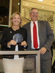 Amy Brunjes of FPL presents a Professional Services Award to Jeff Emmeluth of Craig Jeffries Wealth Management Group.