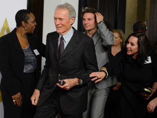"""""""American Sniper"""" director Clint Eastwood, center, and cast member Bradley Cooper are directed onto the arrivals carpet for the annual Academy Awards Nominees Luncheon on Feb. 2, 2015, in Los Angeles."""