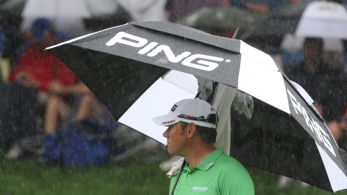 Lee Westwood waits under an umbrella on 2.