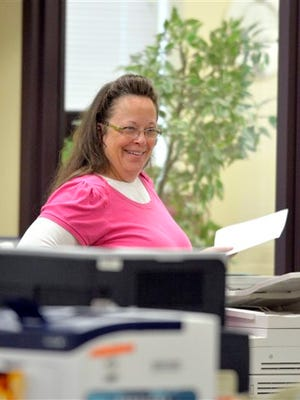 Rowan County Clerk Kim Davis smiles as she helps a customer at the Rowan County Courthouse in Morehead, Ky., Tuesday, Aug. 18, 2015. Davis is back at work and still not issuing marriage licenses while her case is under appeal. U.S. District Judge David Bunning denied Rowan County Clerk Kim Davis' request to delay his ruling from last week ordering her to issue marriage licenses to gay and lesbian couples. That ruling followed the U.S. Supreme Court's decision in June legalizing same-sex marriage nationwide. But Bunning then delayed his own decision, effectively granting Davis' request while also denying it.