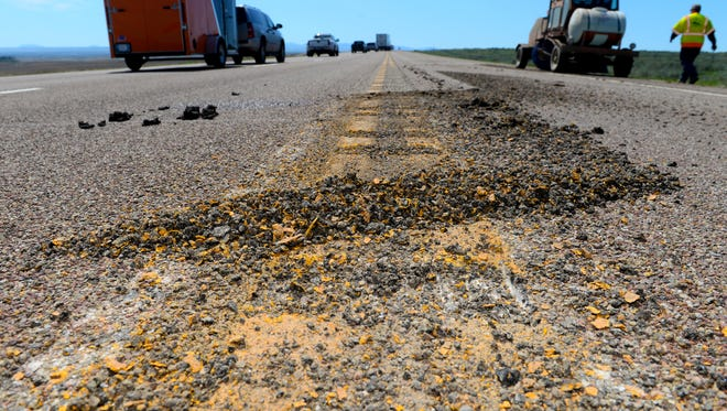 Pieces of asphalt cut from the centerline to make a rumble strip on Highway 87 north of Loma, Thursday.