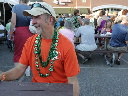 Bob Robinson of Rothschild sports an orange T-shirt and green necklaces at Irishfest in the Basil parking lot in Weston.