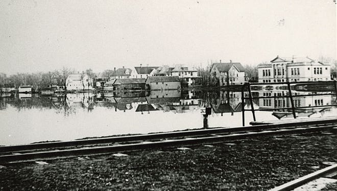 This undated photograph taken in Neenah shows the rear side of the original Carnegie building (Neenah Public Library) along the Fox River on the far right.