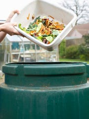 Person pouring kitchen waste into compost bin.