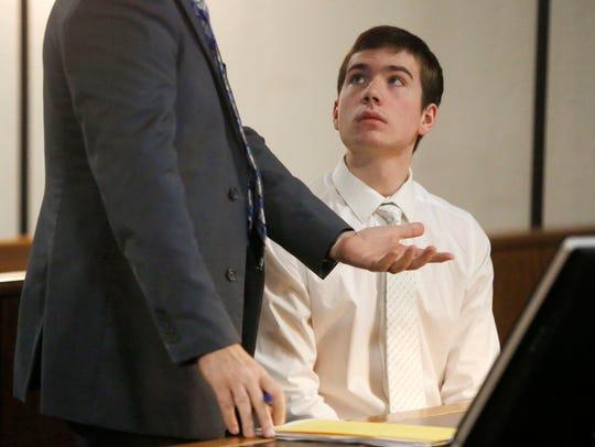 Noah Lamar, 15, looks up at attorney Cory McClure as