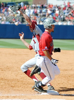 Mississippi's Braxton Lee, right, is safe at first on a bunt as Arkansas second baseman Brian Anderson (1) drops the ball in Oxford, Miss., Saturday, May 3, 2014. (AP Photo/The Oxford Eagle, Bruce Newman) MAGAZINES OUT; NO SALES; MANDATORY CREDIT