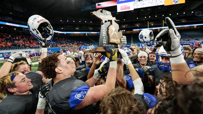Grand Rapids Catholic Central players celebrate after defeating Edwardsburg 42-31 at the MHSAA Division 4 championship game at the Ford Field in Detroit, Friday, November 24, 2017.