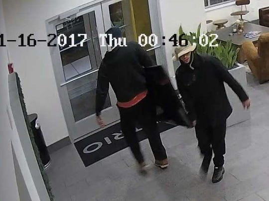 Two men are captured in a surveillance photo stealing a TV from a Walker's Point building