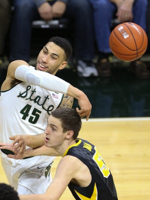 Michigan State's Denzel Valentine passes against Iowa's Nicholas Baer during the first half of MSU's loss Thursday at the Breslin Center.