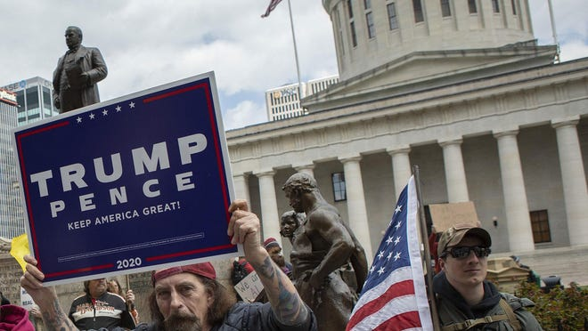 A man carries a President Donald Trump re-election poster at a Statehouse rally on Saturday, April 18, 2020, protesting Ohio Gov. Mike DeWine's stay-at-home order to combat the coronavirus pandemic. Trump carried Ohio by 8 points in 2016, but recent polls show him trailing former Vice President Joe Biden in the state.