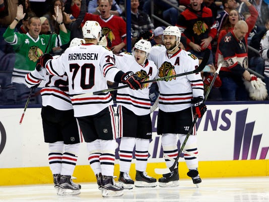 Chicago Blackhawks' Patrick Kane, center, and Brent Seabrook, right, celebrate Kane's goal against the Columbus Blue Jackets with teammates during the first period of an NHL hockey game Saturday, April 9, 2016, in Columbus, Ohio. (AP Photo/Jay LaPrete)