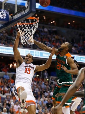 Virginia guard Malcolm Brogdon (15) is fouled by Miami forward Kamari Murphy (21) during the second half of an NCAA college basketball game in the Atlantic Coast Conference tournament, Friday, March 11, 2016, in Washington.  Virginia defeated Miami 73-68.   (AP Photo/Steve Helber)