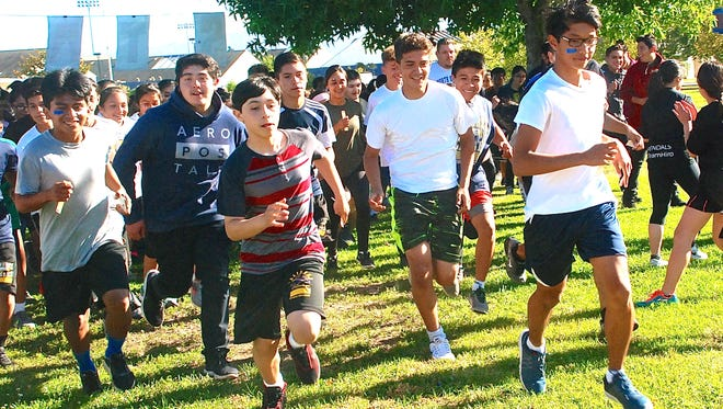 Runners take off on a 5K run Friday at Everett Alvarez High School. The run was a fundraiser to fight Amyotrophic Lateral Sclerosis, a neuromuscular disease that has no known cure.