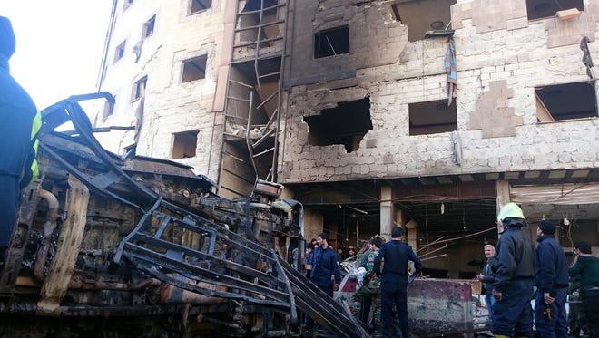 Syrian people and soldiers inspect the site of bombings in southern Damascus, Syria, on Jan. 31, 2016.