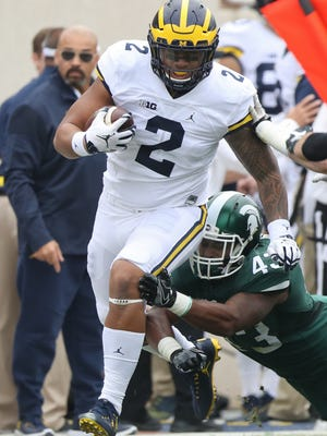 Michigan TE Devin Asiasi runs with the ball as Michigan State LB Ed Davis goes for the tackle during the first quarter Saturday in East Lansing.