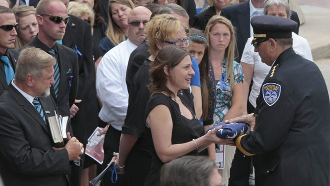 Rochester Police Chief Michael Ciminelli presents the US flag to Amy Pierson, wife of slain Rochester Police Officer Daryl Pierson, during his funeral service.