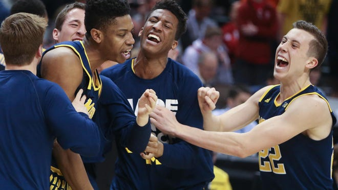 U-M's bench celebrates with sophomore Kameron Chatman after he hit the game-winning three-pointer against Indiana in the Big Ten quarterfinals Friday at Indianapolis.