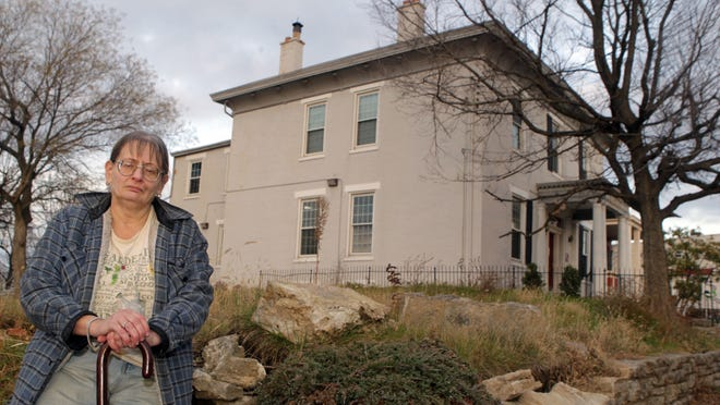 Lydia Karlo, of Corryville, outside an 1853 Greek Revival style structure built by Joseph Herron, an early educator in the city. Karlo is shown outside the 108 William Howard Taft Road building November 25, 2014. Site demolition has started. She opposes the demolition and other new construction in the area because it is changing the architectural character of the neighborhood.
