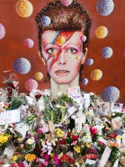 Floral tributes are seen beneath a mural of British singer David Bowie, painted by Australian street artist James Cochran, aka Jimmy C, the day after the announcement of Bowie's death in Brixton, south London.