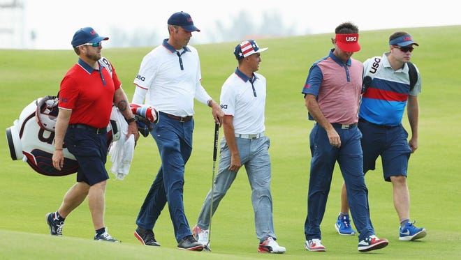 Matt Kuchar, Rickie Fowler and Bubba Watson of the United States walk down a fairway with their caddies during a practice round on Day 4 of the Rio 2016 Olympic Games at Olympic Golf Course on August 9, 2016 in Rio de Janeiro, Brazil.