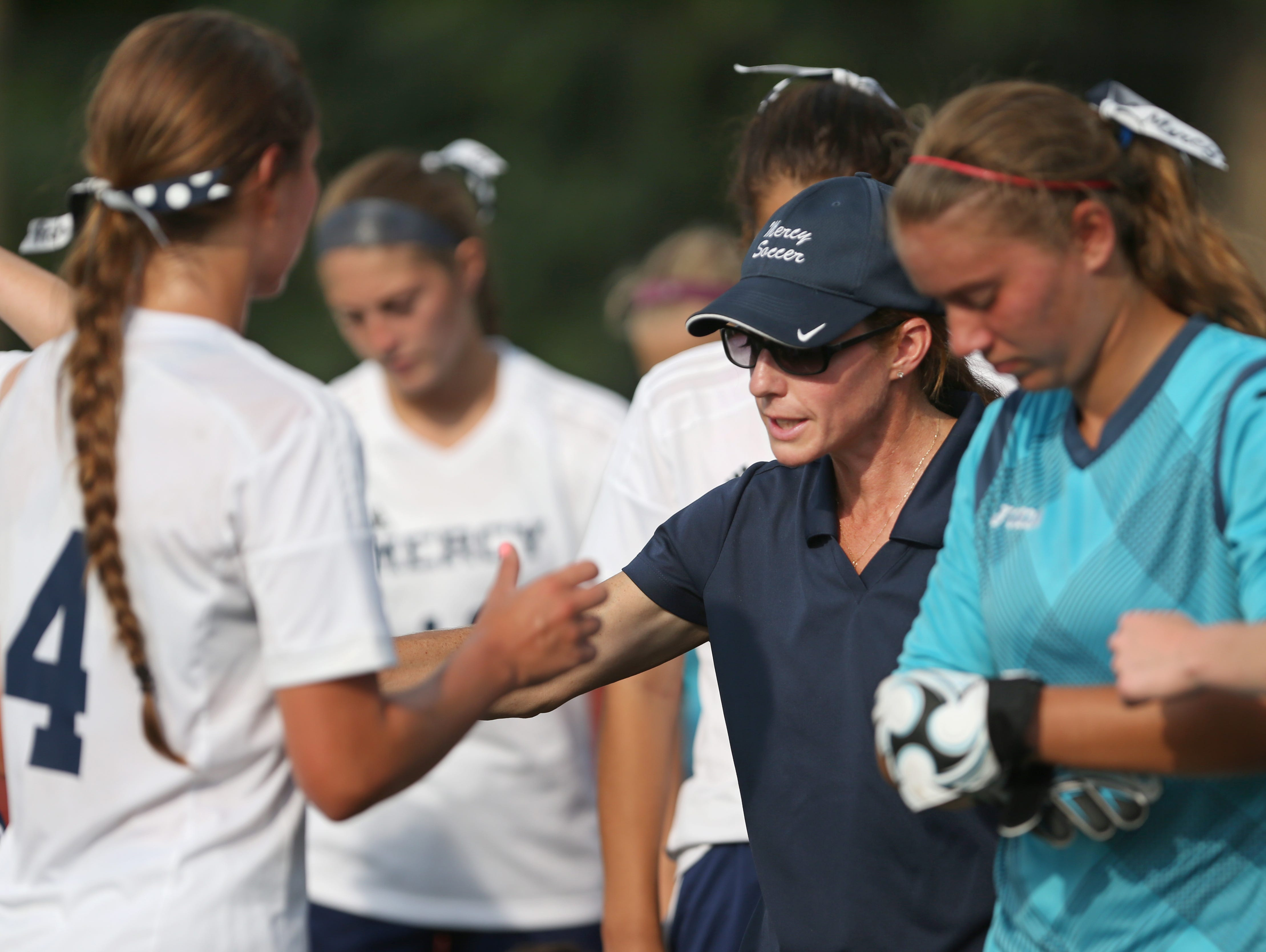 Donna Trost, head coach of Mercy varsity girls soccer, circles up her team for one last pep talk before they take the field during Mercy's matchup against Aquinas at Mercy High Tuesday, Sept. 8, 2015 in Brighton. Trost is the latest winner of the Democrat & Chronicle Coaches Who Care award.