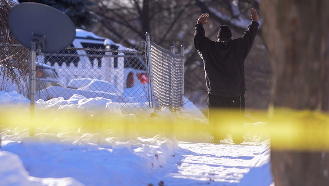 A man exits a home on the 900 block of Maryland Avenue near East Oakland Avenue Thursday, Dec. 15, 2016 in Lansing at the request of Lansing police. Police were on the scene in connection with a shooting that took place overnight.