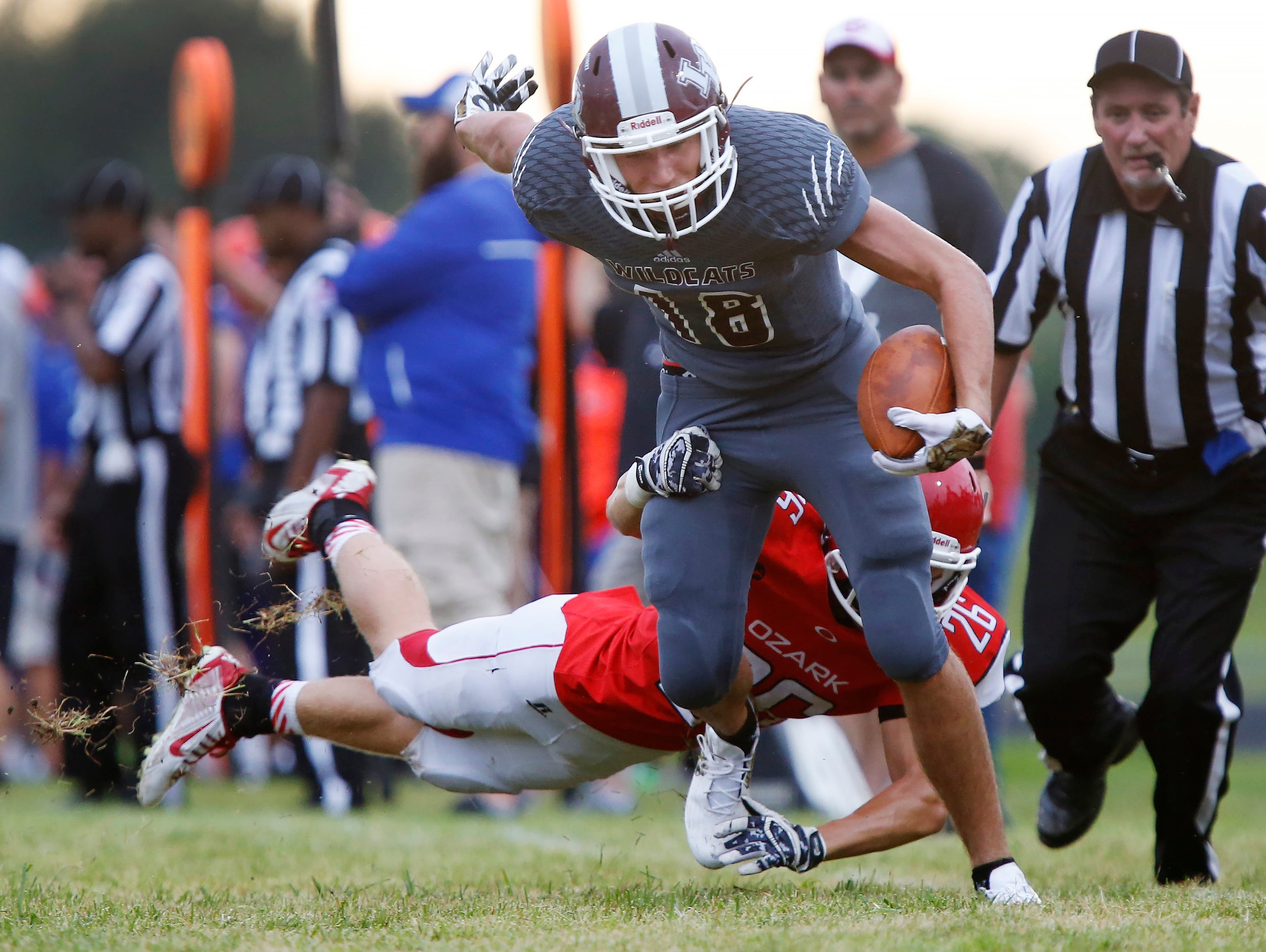 Ryker Strong, of Logan-Rogersville (18), tries to shake free of Ozark's Reed Herrold during the jamboree at Logan-Rogersville High School on Friday, August 12, 2016.