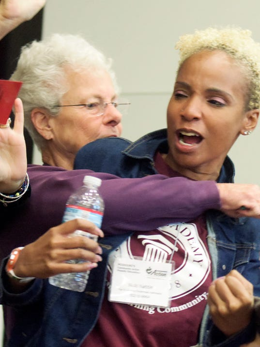 """""""Teacher"""" Marian Rubach of Dover Township breaks up a fight involving Sakeenah Peete of York City, playing the role of an eight-year-old boy with learning disabilities, during a Community Action Poverty Simulation at Logos Academy Friday, Oct. 2, 2015. The two were playing roles in the exercise which serves to sensitize participants to the struggles of poverty. Logos staff took part in the simulation presented by York College. Bill Kalina - bkalina@yorkdispatch.com"""