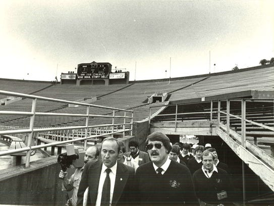 Coach Hayden Fry and his team tour the stadium during