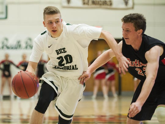 Rice's Elliot Nelson (20) drives to the hoop past Rutland's