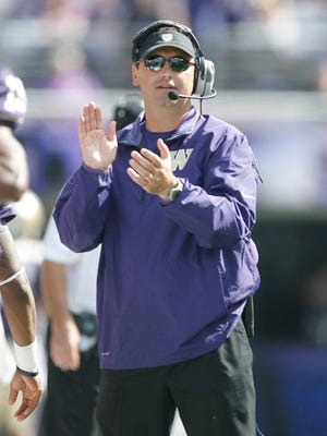 Washington coach Steve Sarkisian applauds his team after a touchdown against the Idaho State Bengals during the first quarter at Husky Stadium.