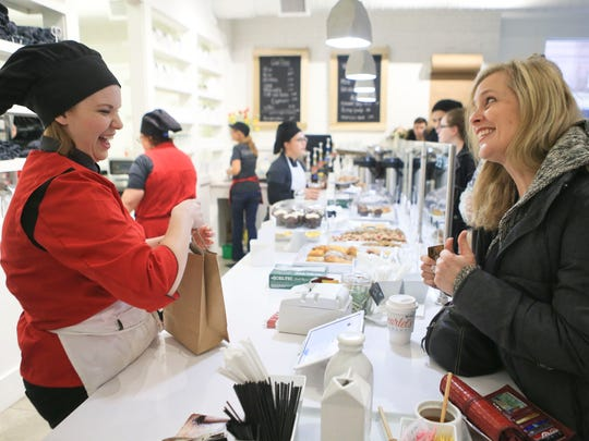 Customer Jennifer Johnson, right, laughs while talking with Rachel Eichberger, business development manager and cashier, at the grand opening of Scarlet's Bakery on East Oak Street in the Shelby Park neighborhood.