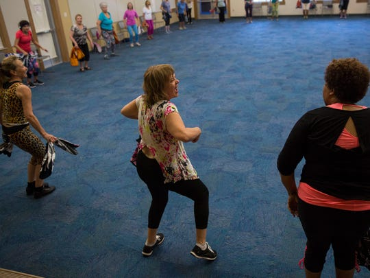 Nancy Robustelli, center, smiles while dancing during Aerobics with Soul at the South Regional Library on Monday, March 19, 2018.