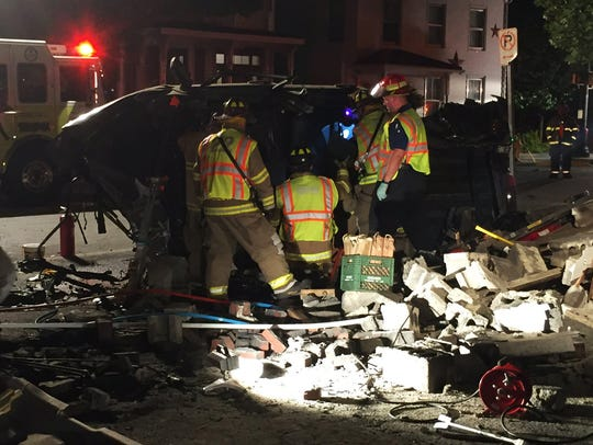 Authorities work at the scene after a car crashed into