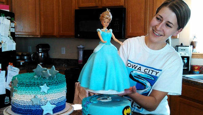 "Missy Ortman calls the cake at right a ""half and half."" The birthday girl to receive it likes princesses, so this Barbie dominates with an edible fondant dress. Half of the cake will be Batman themed, however, to please the boys attending the party."