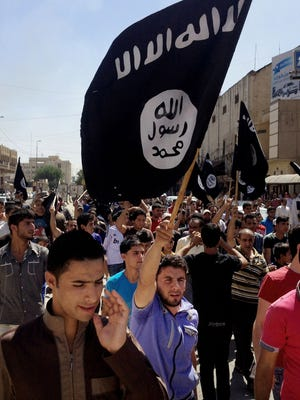 Demonstrators chant pro-Islamic State group slogans as they wave the group's flags June 16, 2014, in front of the provincial government headquarters in Mosul, Iraq.