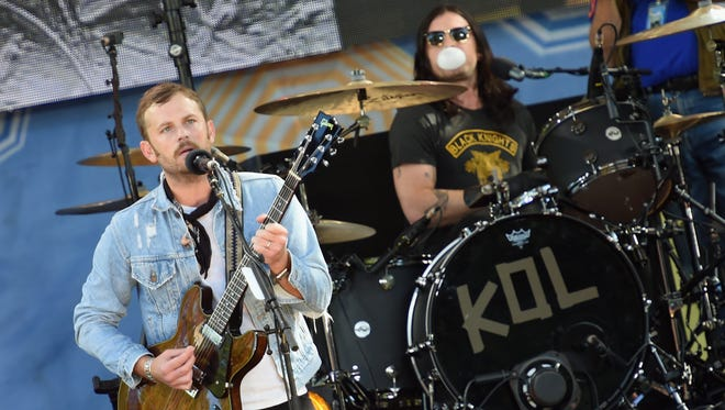 Kings of Leon drummer Nathan Followill, seen blowing a bubble in this image, is sidelined with broken ribs. Vocalist-guitarist Caleb Followill is seen at left.