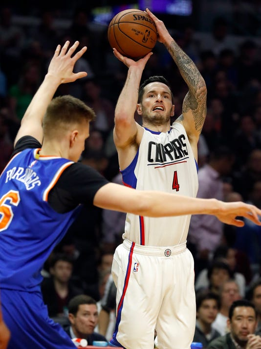 Los Angeles Clippers guard JJ Redick, right, shoots over New York Knicks forward Kristaps Porzingis during the first half of an NBA basketball game, Monday, March 20, 2017, in Los Angeles. (AP Photo/Ryan Kang)