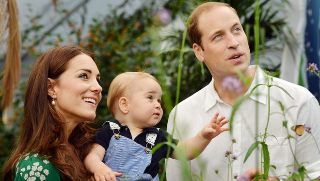 Britain's Prince George's first birthday, shows Prince William (R) and Catherine, Duchess of Cambridge (L) with Prince George during a visit to the Sensational Butterflies exhibition at the Natural History Museum in London on July 2, 2014.