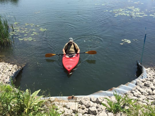 A paddler prepares to enter a culvert carrying the Krispin Blueway under a roadway on Harsens Island. The Michigan Department of Natural Resources and Travel Michigan have launched the Pure Michigan Trail and Trail Town designation program.