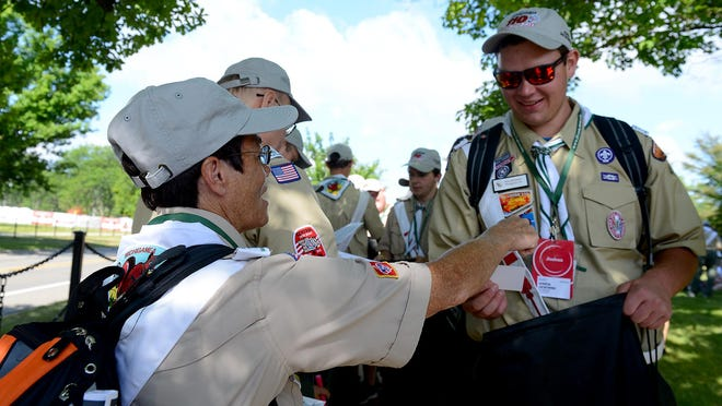 Cheryl Jurincie, with the Michigamea Lodge, which serves northwest Indiana and northeast Illinois, hands out entertaiment tickets to fellow Michigamea scouts as they moved through a line go pick up Order of the Arrow swag Monday outside of Wilson Hall on the campus of Michigan State University.