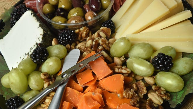 One approach to a holiday party platter is to mix styles of cheese, then add items like olives, nuts and fruit (but no kiwi).