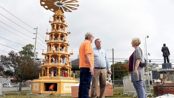 German visitors William Lowery, left, and Claudia Lowery speak with Cullman Mayor Woody Jacobs as the Alabama city's Christmas pyramid is assembled.