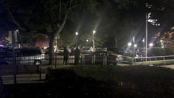 Police investigate the scene of a shooting in the parking lot of a high rise housing complex off Broadway in Providence.