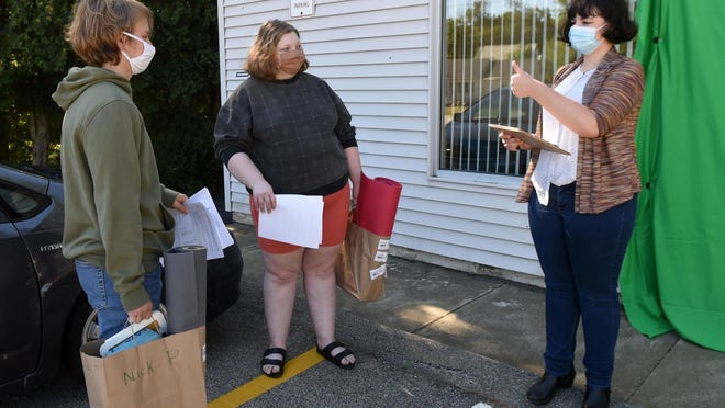 Nick Pezzolesi and Devyn Robin, seniors at Cocheco Academy of the Arts, pick up their school supplies and get information from Alison Frisella on Monday in Dover.