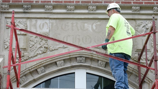 A contractor renovating Locust Street Expressive Arts Elementary School checks his work Thursday while grinding the name of Confederate Gen. Robert E. Lee from stone above the school's entrance. When originally opened in 1904, the school was named for Lee. The name was changed in 2018.
