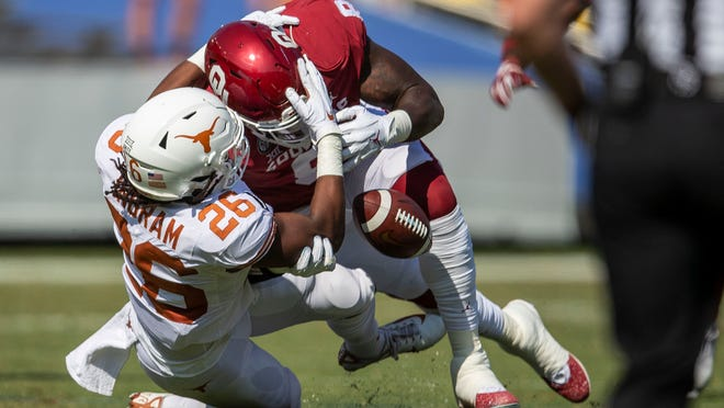 Oklahoma defensive lineman Perrion Winfrey (8) forces a fumble on Texas running back Keaontay Ingram during last season's game at the Cotton Bowl in Dallas.