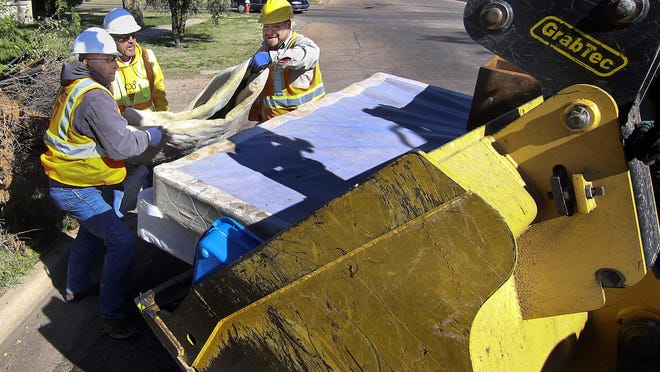 Johnny Ornelas, Roque Flores and Hector Ramirez toss a large roll of carpet and other debris in the bucket of a front end loader in the 900 block of North 12th Street as they and other City Street Department crews work during a past City's fall clean up. This year's fall cleanup is scheduled to begin on Sept. 28.