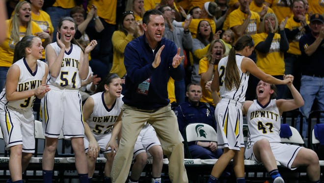 Dewitt's William Winfield and the rest of the bench celebrate a big lead against Saginaw Heritage in their MHSAA Class A semifinal Friday, March 19, 2015, in East Lansing.